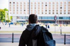 Tourist mit Rucksack von der Rückseite, Rückseite Reisender unter der Stadt, mit dem Gehen von unscharfen Leuten im Hintergrund stockbild
