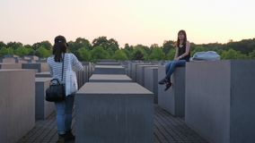 Tourist with mobile phone in hand takes pictures of a girlfriend who sits on gray slab, Holocaust Memorial
