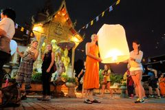 Tourist and monk float a lantern at Yee Peng Stock Photo