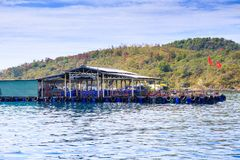 Tourist Moorage Vietnamese Banners by Green Coast Clouds Sky. Tourist moorage with Vietnamese national banners near green hills coast against white clouds lace Royalty Free Stock Photography