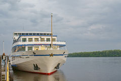 Tourist motor ship moored to pier of river royalty free stock photography