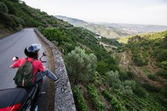 Tourist on a motorbike rides on a serpentine road to the viewpoint of the Douro Valley, Porto. Portugal stock photos