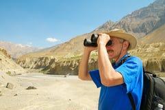Tourist in mountains looking through binoculars Stock Photos