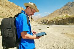 Tourist in mountains looking map on gadget. Europian male tourist in mountains looking map on the electronic device royalty free stock images