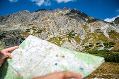Tourist in mountains read the map Stock Images