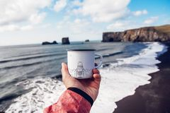 Tourist mug in hand with the image of the mountains on the background of the sea stock images