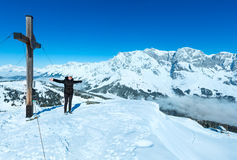 Tourist near the cross on winter mountain top Stock Photo
