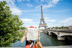 Tourist near the Eiffel tower. Young woman tourist sitting with paper map in front of the Eiffel tower in Paris Royalty Free Stock Image