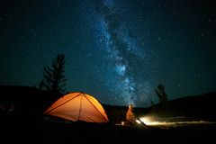 Tourist near his camp tent at night. Tourist near his camp tent at night under a sky full of stars. Orange illuminated tent Royalty Free Stock Photography