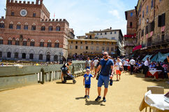 Tourist near Palazzo Publico in Piazza del Campo Town hall of Siena, Tuscany, Italy. View of Palazzo Publico in Piazza del Campo the historic city of Siena in stock photo