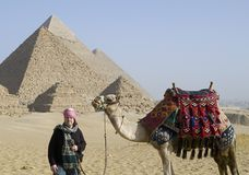 Tourist near pyramids. Tourist with a camel near pyramids in Giza stock image