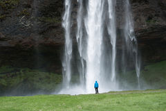 Tourist near a Seljalandsfoss waterfall in Iceland Royalty Free Stock Photography