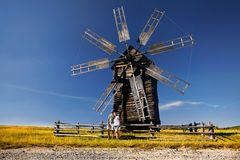 Tourist near wooden wind mill royalty free stock photo