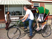 Tourist negotiating price on bike taxi, Volendam. Holland/Netherlands. It is a Cycle rickshaw imported from India Stock Image
