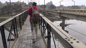 Tourist and Nepalese man on sacred Bagmati river bridge stock footage