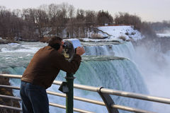 Tourist in Niagara Falls. A tourist wearing a brown coat uses pay binoculars to look at the view of Niagara Falls in the winter royalty free stock photography