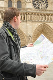 Tourist at Notre Dame, Paris. Tourist holding map in front of Notre Dame, Paris Stock Image