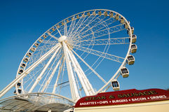 Tourist Observation Ferris Wheel. Observation tourist wheel on Plymouth Hoe England with fast food stall in foreground Royalty Free Stock Photos
