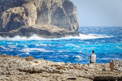 Tourist observe the rough seas of Dwejra Bay in Gozo, Malta Royalty Free Stock Photo