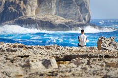 Tourist observe the rough seas of Dwejra Bay in Gozo, Malta Stock Image