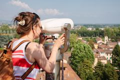 Tourist observing Lucca old town cityscape through tourist telescope Tuscany Italy stock photography