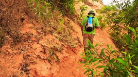 Tourist Old Man Climbs along Fairy-Stream Slope past Plants stock footage