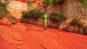 Tourist Old Man Stands in Shallow Water of Fairy-Stream. Tourist old man with backpack stands barefoot in shallow red water of Fairy-Stream against pitted rocks stock video footage