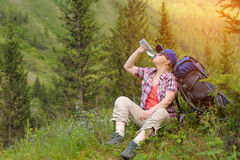 Tourist overcome obstacles resting and drinking clean water. Stock Photography