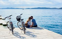Tourist pair, man and woman with bicycles on high paved stone sidewalk near sea water on sunny day royalty free stock photography
