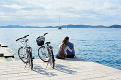 Tourist pair, man and woman with bicycles on high paved stone sidewalk near sea water on sunny day stock photography