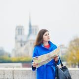 Tourist in Paris, unter Verwendung der Karte nahe Notre-Dame-Kathedrale Lizenzfreie Stockfotografie