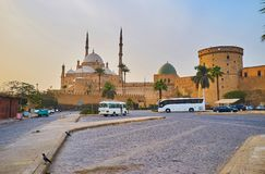 The tourist parking in front of medieval Saladin Citadel with a view on its fortifications and historic mosques - Alabaster and Al. Nasir Muhammad, Cairo, Egypt royalty free stock photography