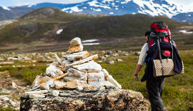 A tourist passing a milestone on a mountain trail. A tourist with a large backpack is passing a pyramid-shaped milestone on a mountain trail. The path leads Royalty Free Stock Photo