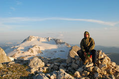 Tourist on peak mountain Stock Image