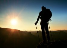Tourist on peak. Sunrise with inversion.Cliff above deep autumn valley with tourist guide on top. Hiker watch breathtaking  beauti Stock Photography