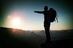 Tourist on peak. Sunrise with inversion.Cliff above deep autumn valley with tourist guide on top. Hiker watch breathtaking  beauti Royalty Free Stock Image