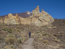 Tourist people hikers on the path around famous pitoresque rock. Formation Roques de Garcia with view on colorful volcano pico del teide highest spanish Stock Images