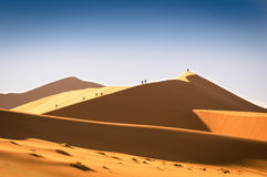 Tourist people hiking on sand dune at Deadvlei near Sossusvlei Royalty Free Stock Image