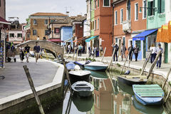 Tourist people walking around canal with colorful houses in beautiful city of Burano. Royalty Free Stock Image
