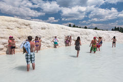 Tourist people are walking on travertines of Pamukkale. Royalty Free Stock Photo