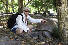Tourist petting a giant tortoise. Seychelles. Royalty Free Stock Photos