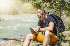 A tourist with a phone and a backpack on the mountains Stock Images