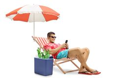 Tourist with a phone sitting in a deck chair with an umbrella ne. Xt to a cooling box isolated on white background royalty free stock photography