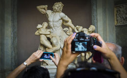 Tourist photograph the Laocoon Sculpture in the Vatican Museum, Vatican City, Rome, Italy. Royalty Free Stock Images