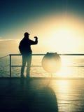 Tourist photograph  on sea mole. Hiker take photos of morning sea. Autumn fog. Tourist on wooden board in wharf, Sunny sky, sm Stock Image