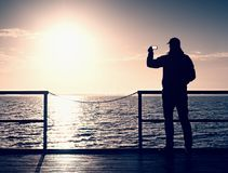 Tourist photograph  on sea mole. Hiker take photos of morning sea. Tourist on wooden board. In wharf, Sunny sky, smooth water level Royalty Free Stock Photo