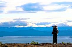 Tourist-photographer. Kamchatka. Tourist takes a snapshot of the ocean bay and mountains of Kamchatka Stock Image
