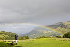 Tourist photographer taking picture of rainbow stock photography