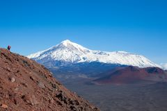 A tourist photographer at the top of the mountain takes pictures of the landscape of volcanoes. Kamchatka stock photography