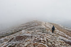 Tourist photographer with tripod on hand walking on frozen hill. With fog Royalty Free Stock Images